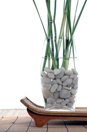 Bamboo and grasses in a white stone filled vase set upon a organic tray.