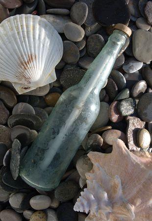 Boodschap in een fles op een natte stoney strand met schelpen.