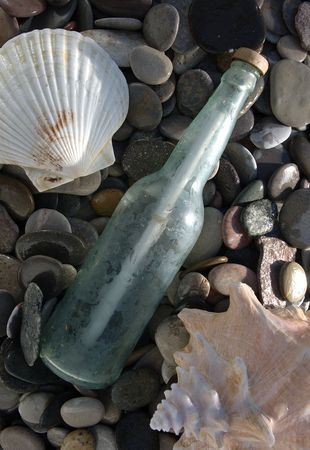 Message in a bottle on a wet stoney beach with seashells.