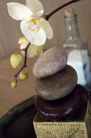 Spa objects: orchid, water, stones, and a bottle of sea salt.