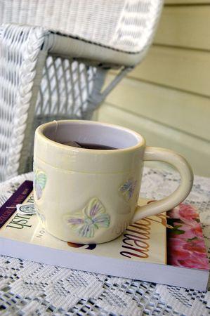 De perfecte kop thee, alles over het vrouwelijk .... zacht geel, butterflys op de beker, en een boek met rozen op de cover. Stockfoto