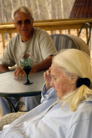 Groot Grootmoeder met problemen. Het is wellicht aan alcohol gerelateerde zie glas wijn op tafel. Haar zoon is senior op de achtergrond.