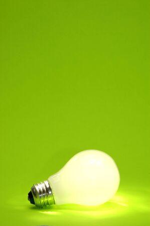 electric bulb: A lit light bulb on green.