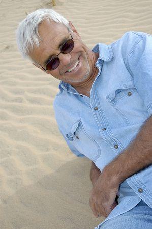 Casual vertrouwen senior man ontspannen op een duin.