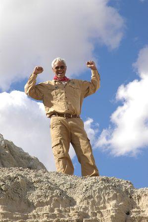 Triomfantelijke senior man na klom naar de top van een berg woestijn. om alle vier van de beelden in deze serie trefwoord: khaki  man Stockfoto