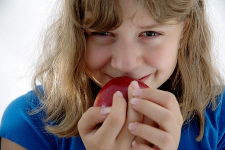 mischievious: Close up of an adolescent girl with an apple and a mischievious smile.