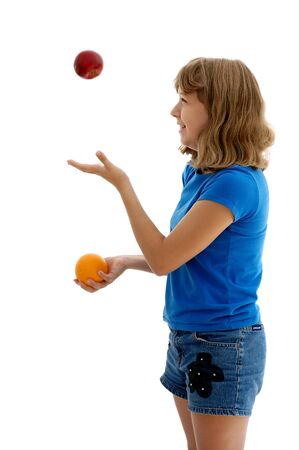 13 year old girl juggling an apple and an orange, photographed on white. photo