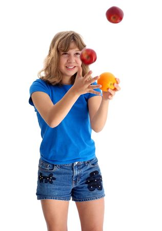 Adolescent girl juggling apples and oranges photographed on white. Stock Photo
