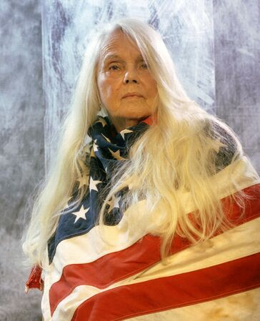Patriotic senior woman with long silver hair wrapped in the American flag.