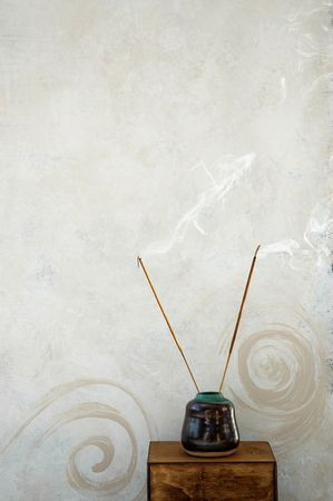 ладан: Incense burning next to a rustic spa wall painted with spirals. Фото со стока