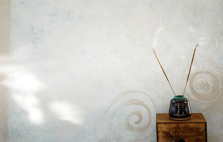 Incense burning next to a rustic spa wall painted with spirals. Stock Photo