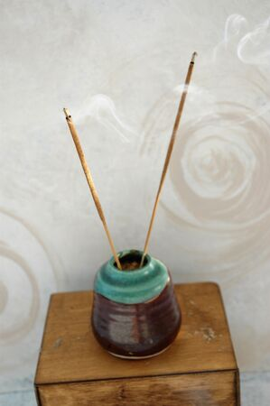Incense burning next to a spiral painted wall. Shallow depth of field, focus on the foreground stick. Stock Photo