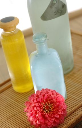 Bottles and a flower in a natural setting. The Chinese character on the green bottle means