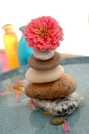 A stone carintower in a basin topped by a flower with spa bottles in the background. Stock Photo