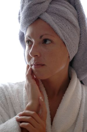 Portrait of a young woman after her bath with her head wrapped in a towel and wearing a bathrobe.