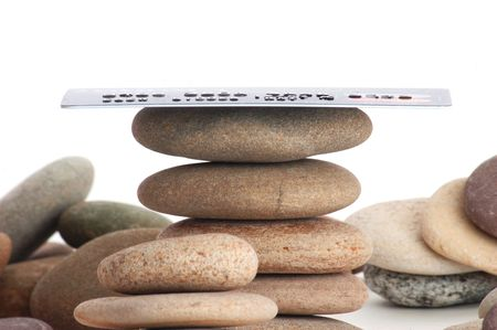 partially: Credit card and stacked stones on white. Note: all logos have been obscured andor partially cloned out.This is not an activated credit card.