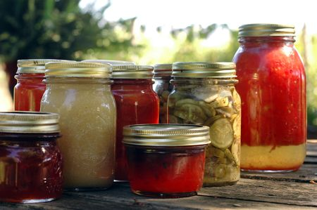 Homemade preserves sitting on a rustic table outside. Pickels, tomatoes, appplesauce, etc. Stock Photo