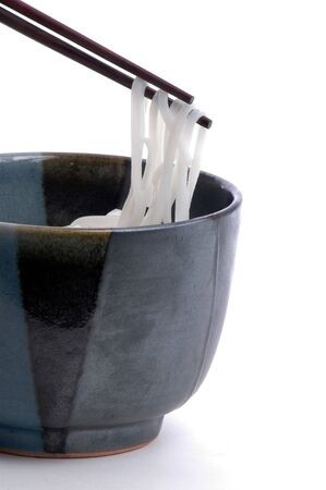 Asian rice noodlesbeing raised from a glazed ceramic bowl with chopstix. Isolalted on white.