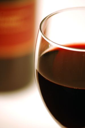 Close up of red wine in a glass with a bottle in the background. Extreme shallow depth of focus.
