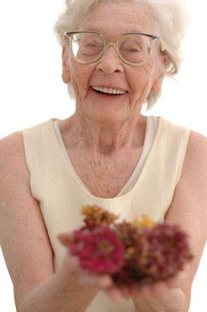 Oudere vrouw in haar tachtig lachend Cupping bloemen met haar handen. Gefotografeerd op wit. Stockfoto