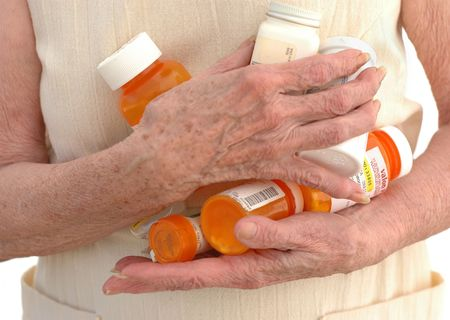 clutching: The hands of a senior woman clutching many meds.