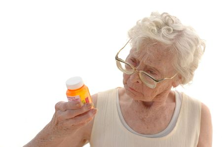 Mature woman in her eighties trying to read a medicine bottle. Stock Photo