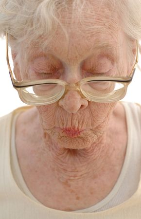 Sharp Mature woman in her eighties looking down with her big glasses. Stock Photo