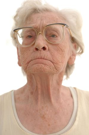 mean: Portrait of a stubborn mature woman in her eighties. Photographed on white. Stock Photo