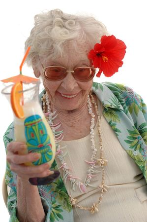 Super senior 80 year old Bahama Mama Granny with a tropical drink and Hibiscus flower in her hair.