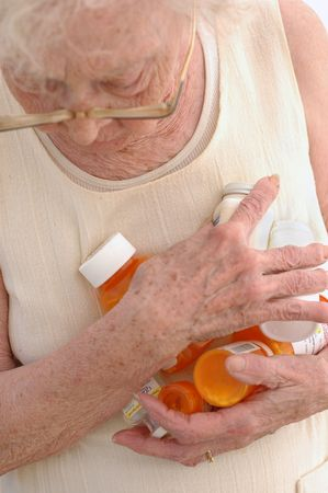 maturity: Mature woman clasping prescription bottles.