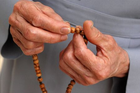 Hands of a mature catholic nun counting the rosary. Stock Photo