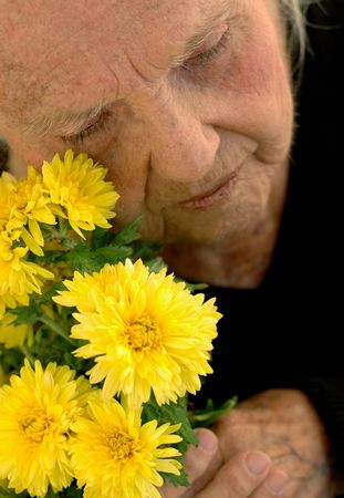 great grandmother:  broken great grandmother. Close up with yellow Mums. Woman in her eighties.