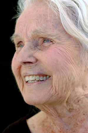 Lachend grote grootmoeder. Close-up portret op zwarte achtergrond. Vrouw in haar jaren tachtig.