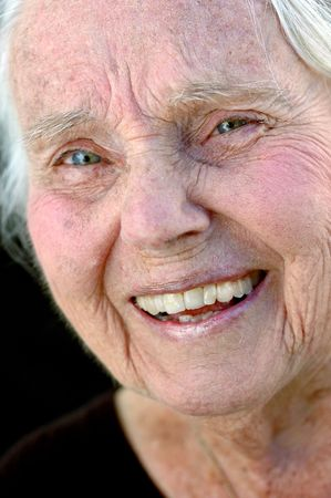 Lachend grote grootmoeder. Close up op een zwarte achtergrond. Vrouw in haar jaren tachtig.