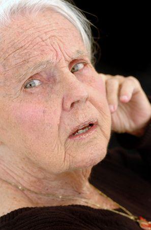 Disturbed great grandmother, close up on black background. Woman in her eighties. Banco de Imagens