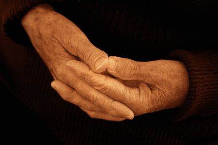 The calm composed hands of an 80 year old woman. Black and white sepia toned. Stock Photo