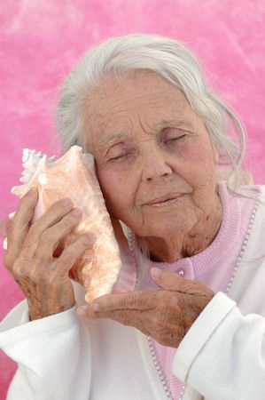 aging brain: Smiling great grandmother listening to a seashell. Pink background. Woman in her eighties. Stock Photo