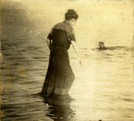 fading: Vintage woman wades in towards a swimming man. Circa 1910. Photo very old with many scratches, fading. and solarizing qualities. Stock Photo