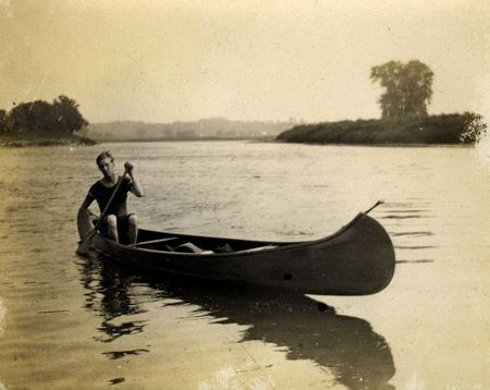 paddler: Vintage Canoe paddler. Circa 1909 print has many scratches, artifacts, fading, and solarization qualities. Stock Photo