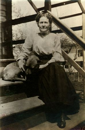 vintage photo: Vintage Pet Owner, woman with dog. Circa 1912 print has scratches, artifacts, fading and solarization qualities.
