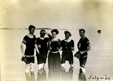 Vintage zwemmers goofing uitgeschakeld met hun schoenen in het water. Circa 1910 print heeft krassen, artefacten, fading en solarization kwaliteiten. Stockfoto
