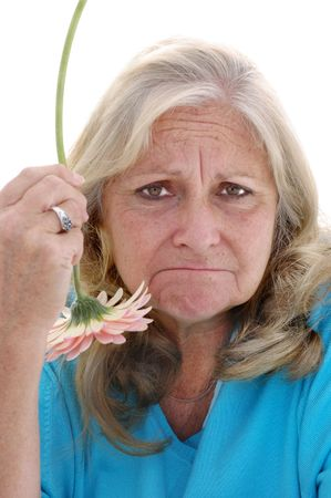 Funny faced woman in her late fifties holding a pink Gerbera flower upside down, photographed on a white background. photo