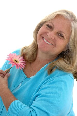 Woman in her late fifties holding a pink Gerbera flower on a white background.