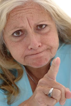 Woman in her late fifties pointing her finger in a funny faced warning, photographed on a white background. Stock Photo