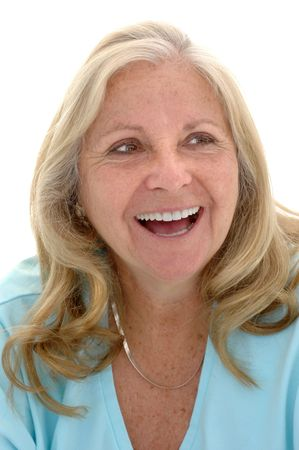 late fifties: Woman in her late fifties with a big smile photographed on a white background.
