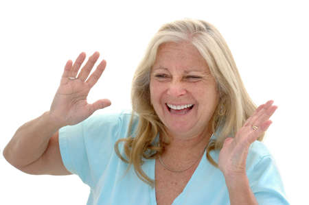 late fifties: Woman in her late fifties laughing photographed on a white background.