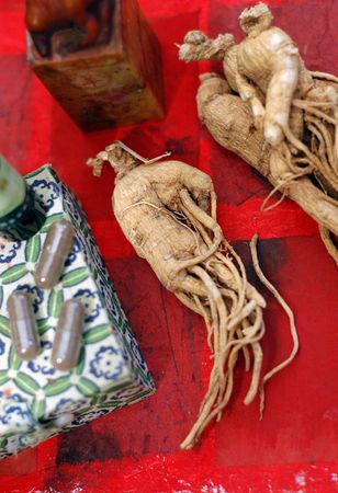 Ginseng, the energy root photograped on a red background with capsules. photo