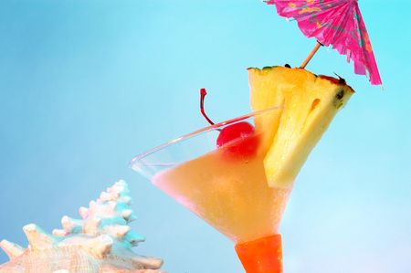 grenadine: Flirtini Martini; pineapple juice, champagne, and grenadine. Photographed with a seashell on a blue lit background.