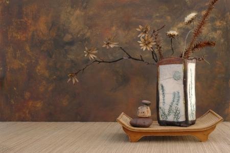 Zen stilleven met Raku vaas, natuurlijk gedroogde bloemen en stenen.