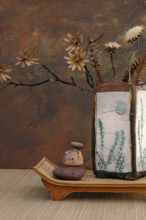 Zen still life with Raku vase, natural dried flowers, and stones.